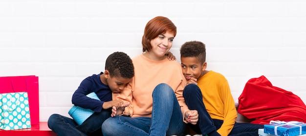 Crianças afro-americanas com sua mãe entre muitos presentes para as férias de natal Foto Premium