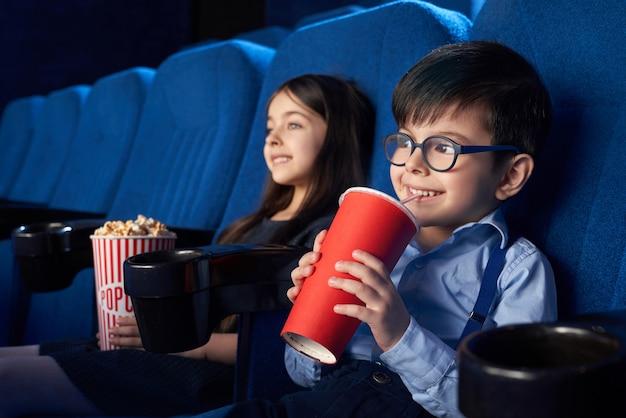 Crianças alegres, assistindo filme, bebendo bebida com gás no cinema. Foto gratuita