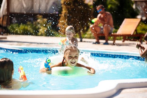 Crianças alegres jogando pistolas, regozijando-se, pulando, nadando na piscina. Foto gratuita