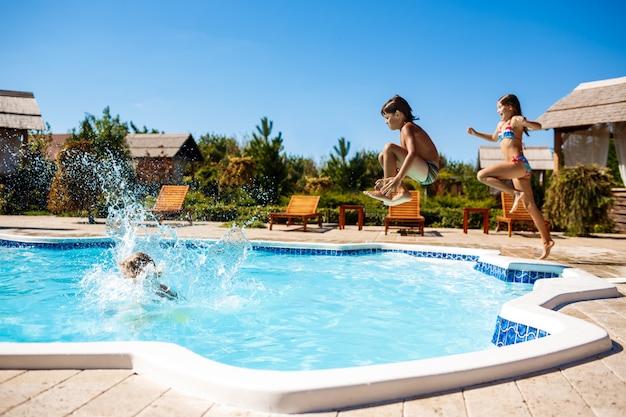Crianças alegres, regozijando-se, pulando, nadando na piscina. Foto gratuita