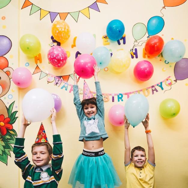 Crianças alegres segurando balões Foto gratuita