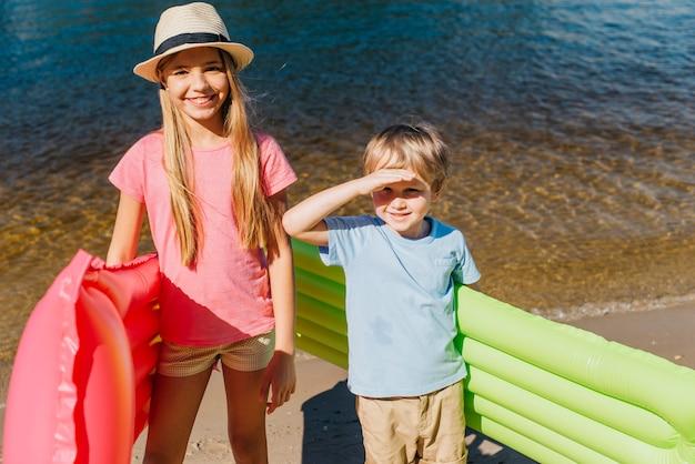 Crianças alegres, sorrindo em dia quente à beira-mar Foto gratuita