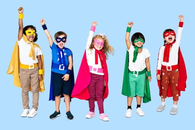 Crianças alegres, vestindo trajes de super-heróis Foto Premium