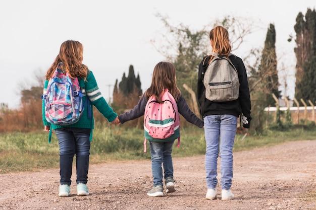 Crianças anônimas caminhando para a escola Foto gratuita