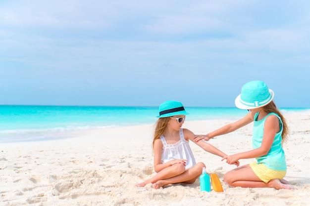 Crianças, aplicar protetor solar uns aos outros na praia. o conceito de proteção contra radiação ultravioleta Foto Premium
