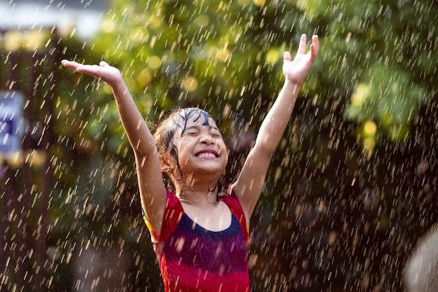Crianças asiáticas brincando na chuva estão felizes. Foto gratuita