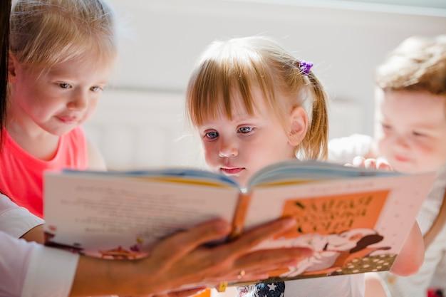 Crianças assistindo livro juntos Foto Premium