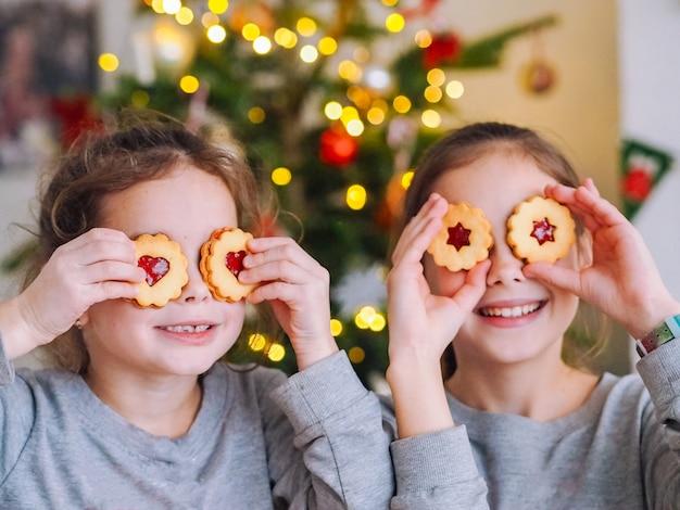 Crianças brincando com biscoitos debaixo da árvore de natal na sala com luzes de natal Foto Premium