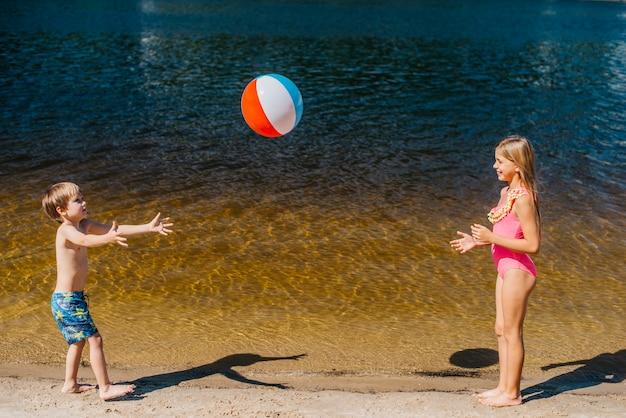 Crianças brincando com bola de praia em pé perto do mar Foto gratuita