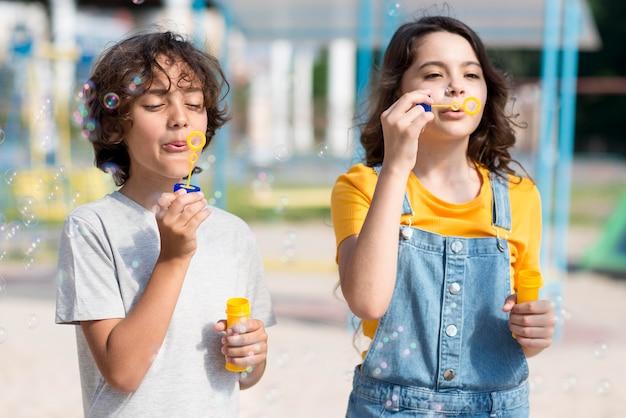 Crianças brincando com soprador de bolhas Foto gratuita