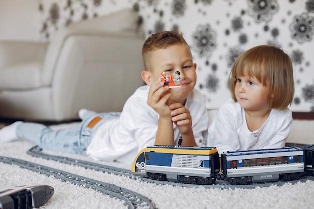 Crianças brincando com trem de lego e brinquedo em uma sala de jogos Foto gratuita
