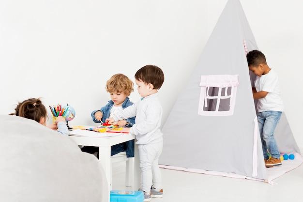 Crianças brincando juntos em casa com a barraca Foto gratuita