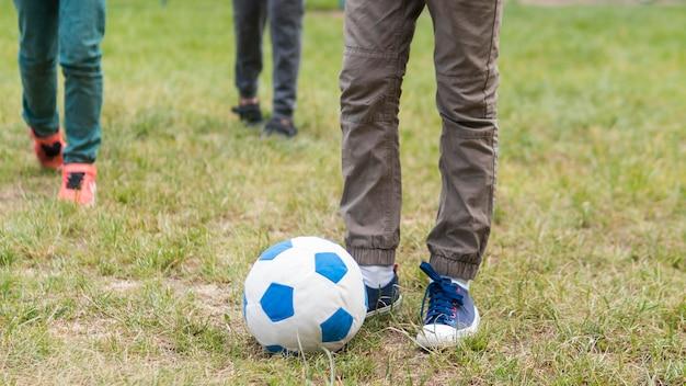 Crianças brincando no parque com bola de futebol Foto gratuita