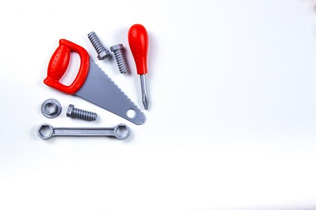 Crianças brinquedos de construção ferramentas: chaves de fenda coloridas, parafusos e porcas em fundo de madeira. Foto Premium