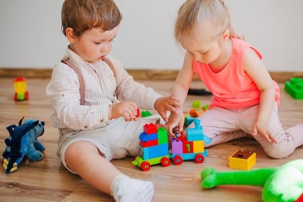 Crianças com brinquedos no chão Foto gratuita