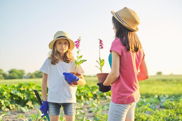 Crianças com flores em vasos, luvas com ferramentas de jardim Foto Premium