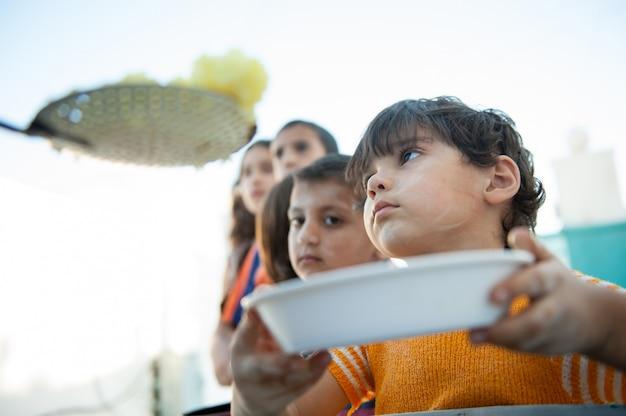Crianças com fome sendo alimentadas por caridade Foto Premium