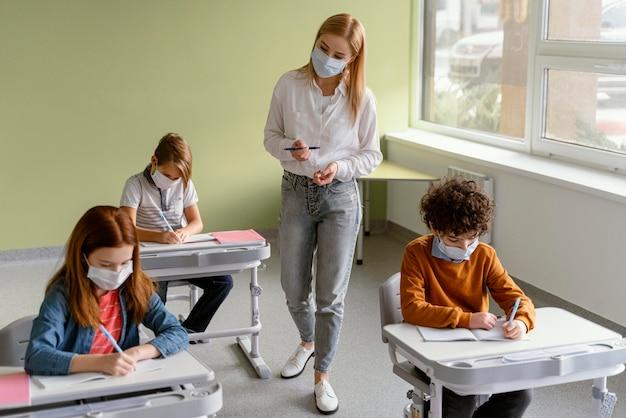 Crianças com máscaras médicas aprendendo na escola com o professor Foto gratuita
