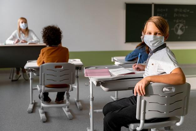 Crianças com máscaras médicas aprendendo na escola com uma professora Foto gratuita