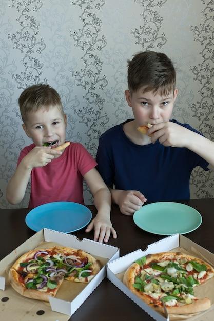 Crianças comem pizza e massa no café. crianças comendo alimentos não saudáveis dentro de casa. Foto Premium