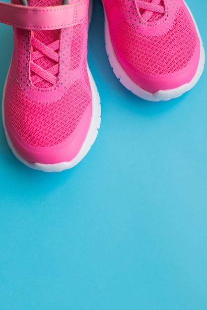 Crianças cor-de-rosa que treinam sapatas isoladas no fundo azul roupa da criança, desgaste do pé e sapatilhas dos esportes do fashion.children. par de sapatas dos esportes da menina. copie o espaço Foto Premium