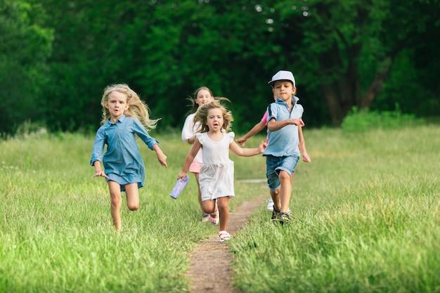 Crianças, crianças correndo no prado, na luz do sol de verão. Foto gratuita