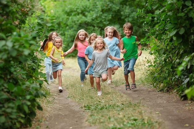 Crianças, crianças correndo no prado verde Foto gratuita