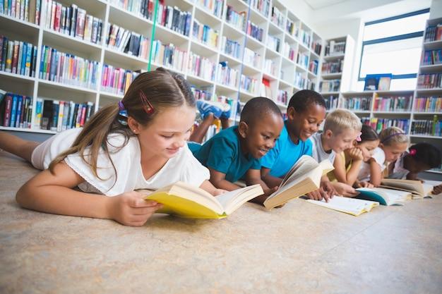 Crianças da escola, deitado no chão, lendo o livro na biblioteca Foto Premium