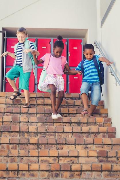 Crianças da escola descer da escada Foto Premium