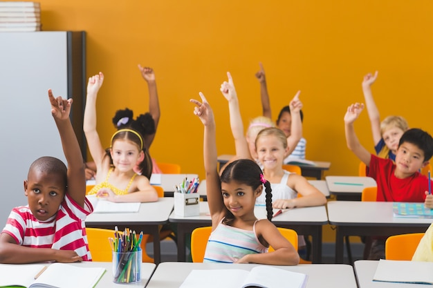 Crianças da escola levantando a mão na sala de aula Foto Premium