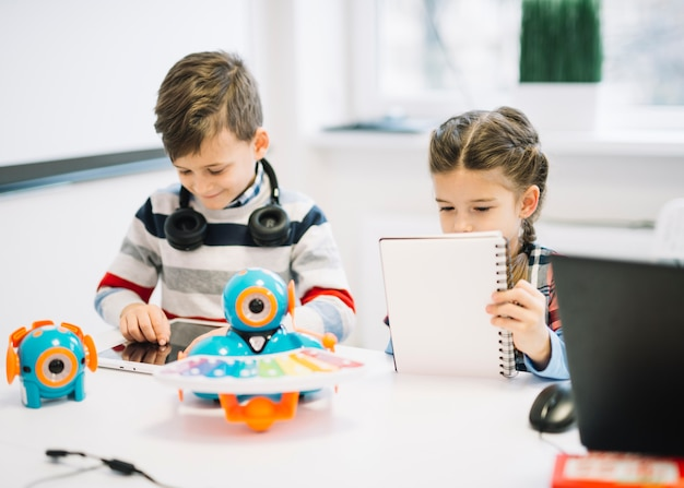 Crianças da escola ocupadas em escrever notas e usando o tablet digital na classe Foto gratuita