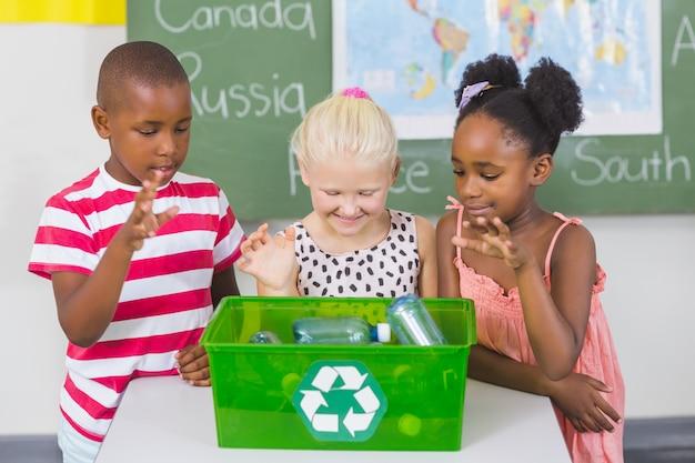 Crianças da escola procurando reciclar caixa de logotipo em sala de aula Foto Premium