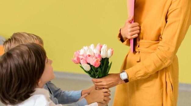 Crianças dando um buquê de flores ao professor Foto gratuita