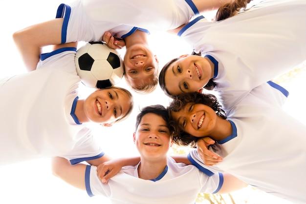 Crianças de ângulo baixo em roupas esportivas olhando para baixo Foto gratuita