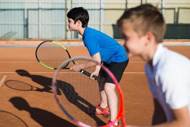 Crianças de lado jogando tênis de duplas Foto gratuita