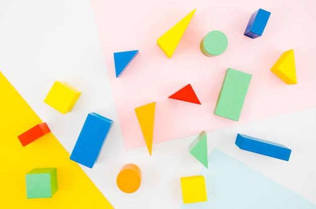 Crianças de madeira vista superior brinquedos com fundo colorido Foto gratuita