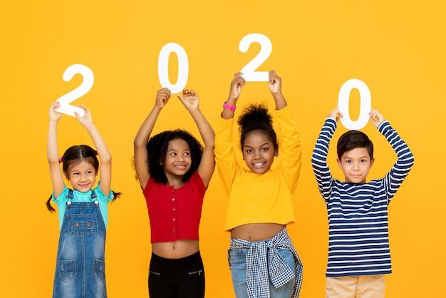Crianças de raça mista bonito sorrindo e segurando os números 2020 Foto Premium