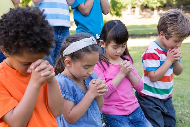 Crianças dizendo suas orações no parque Foto Premium