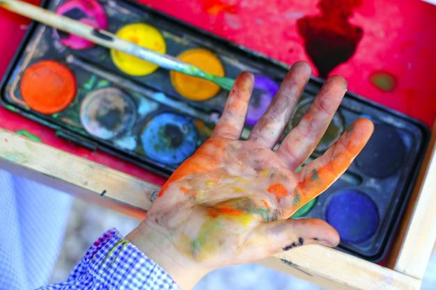 Crianças do artista que pintam as mãos da escova Foto Premium