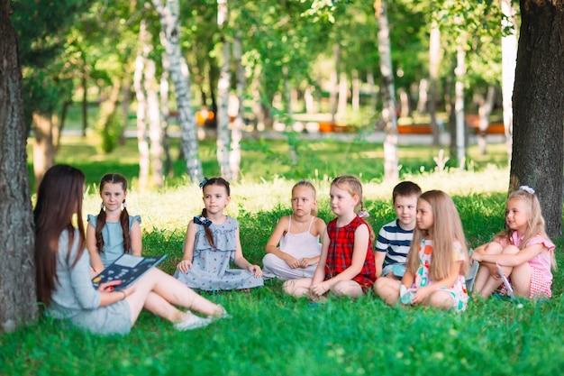 Crianças, e, educação, mulher jovem, no trabalho, como, professor, livro leitura, para, meninos meninas, parque Foto Premium