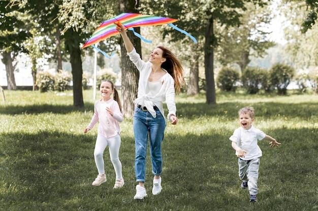 Crianças e mãe brincando com pipa colorida Foto gratuita