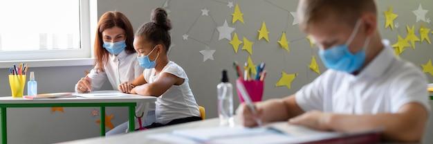 Crianças e professores usando máscaras médicas na sala de aula Foto gratuita