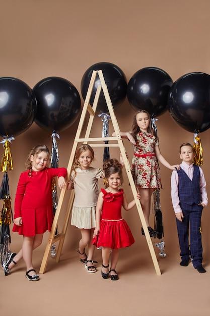 Crianças elegantes em vestidos de noite e trajes comemorando o primeiro dia de aula. Foto Premium