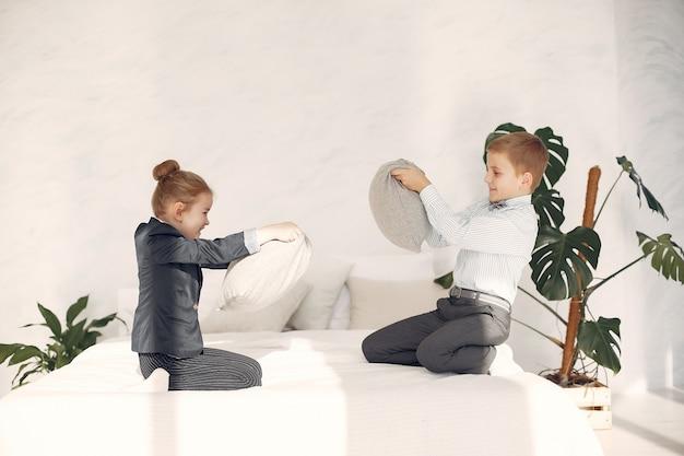 Crianças em casa lutam travesseiros Foto gratuita