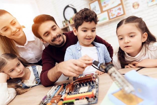 Crianças em conjunto com o professor trabalham com um ferro de solda. Foto Premium