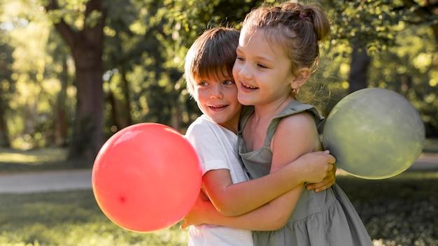 Crianças em fotos médias se abraçando ao ar livre Foto Premium