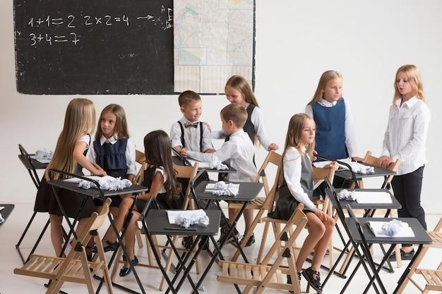 Crianças em idade escolar na sala de aula na lição Foto gratuita