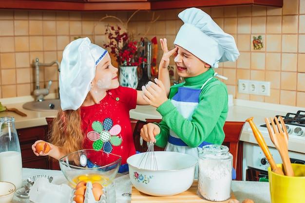 Crianças engraçadas família felizes estão preparando massa, assar biscoitos na cozinha Foto gratuita
