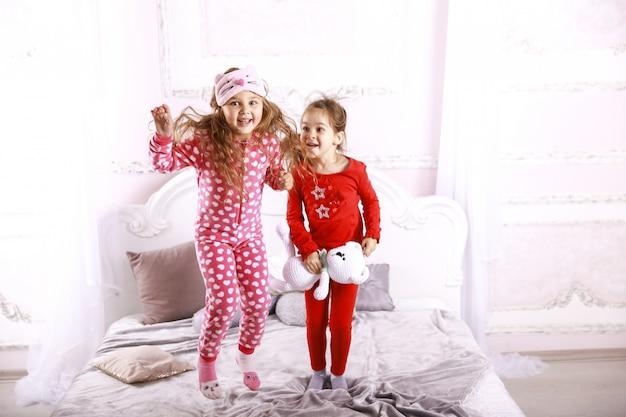 Crianças engraçadas felizes, vestidas com pijamas brilhantes estão pulando na cama e brincando juntos Foto gratuita