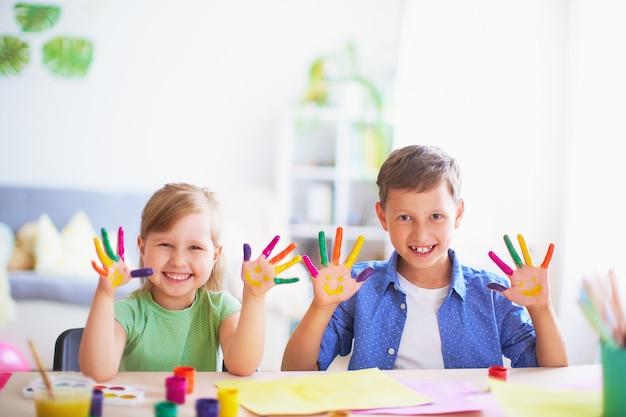Crianças engraçadas mostram as palmas das mãos a tinta pintada. Foto Premium